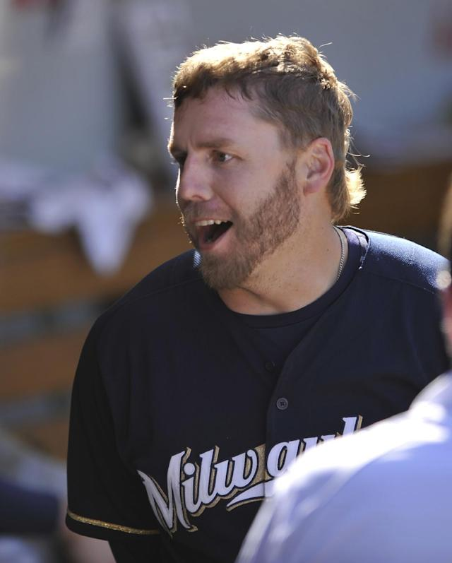 Milwaukee Brewers' Mark Reynolds celebrates with teammates in the dugout after hitting a solo home run during the eighth inning of a baseball game against the Chicago Cubs in Chicago, Thursday, Aug. 14, 2014. (AP Photo/Paul Beaty)
