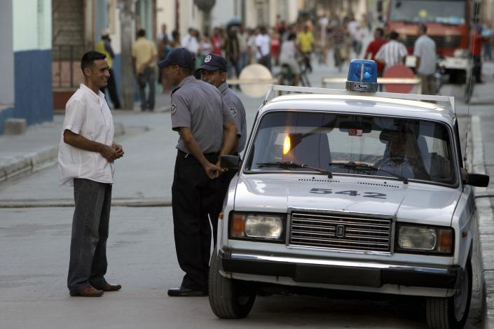 A security officer talks to two police officers outside the courthouse where Spanish citizen Angel Carromero is on trial in Bayamo, Cuba, Friday, Oct. 5, 2012. Authorities accused Carromero of speeding and charged him with the equivalent of vehicular manslaughter, and prosecutors asked the court for a seven-year sentence. The car crash killed a prominent Cuban dissident Oswaldo Paya and another dissident, Harold Cepero on July 22. A panel of judges will now consider the evidence and issue a ruling at an unspecified future date. (AP Photo/Franklin Reyes)