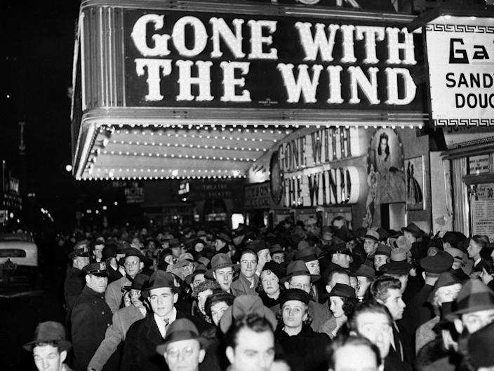"In this Dec. 19, 1939 file photo, a crowd walks past the Astor Theater during the Broadway premiere of ""Gone With the Wind"" in New York. A Memphis, Tennessee, theater has cancelled an annual screening of the classic 1939 film because of racially insensitive content."