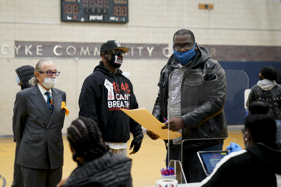 Terrence Floyd, brother of George Floyd, center, waits with Sandy Rubenstein, left, as Rev. Kevin McCall picks up his ballot to vote, Tuesday, Nov. 3, 2020, in the Brooklyn borough of New York. (AP Photo/Frank Franklin II)