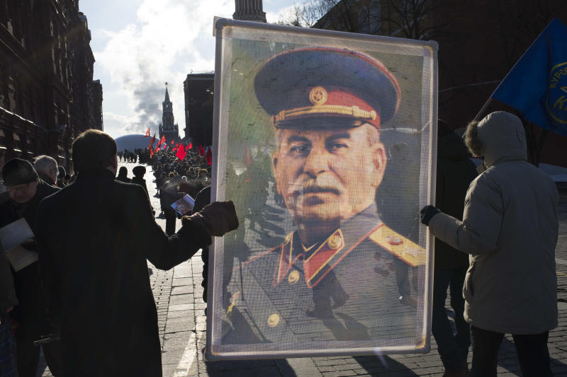 Communist supporters carry a portrait depicting Soviet dictator Josef Stalin as they line up to place flowers on Stalin's grave in Red Square, outside the Kremlin wall to mark the 60th anniversary of his death, Moscow, Russia, Tuesday, March 5, 2013. Stalin led the Soviet Union from 1924 until his death in 1953. Communists credit him with leading the country to victory in World War II while others condemn the brutal purges that killed millions. (AP Photo/Alexander Zemlianichenko)