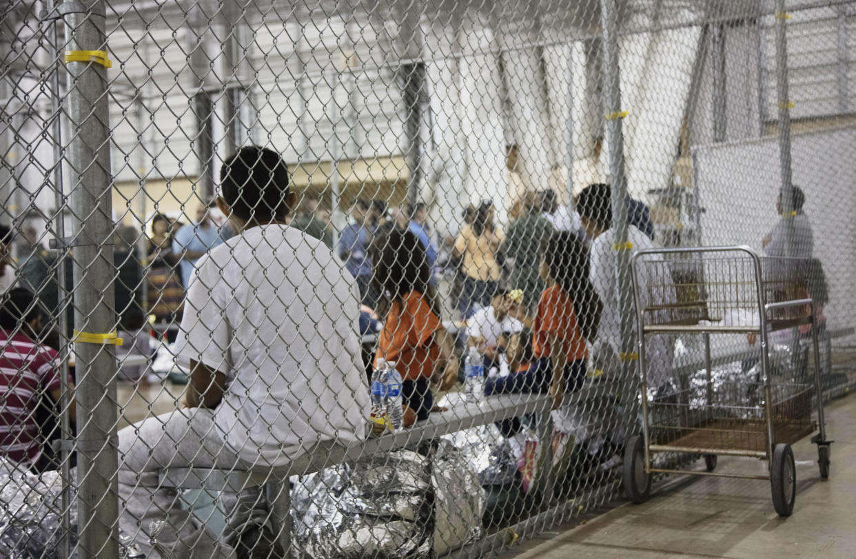 People who have been taken into custody related to cases of illegal entry into the United States sit in one of the cages at a facility in McAllen, Texas, Sunday, June 17, 2018. (Photo: U.S. Customs and Border Protection's Rio Grande Valley Sector via AP)