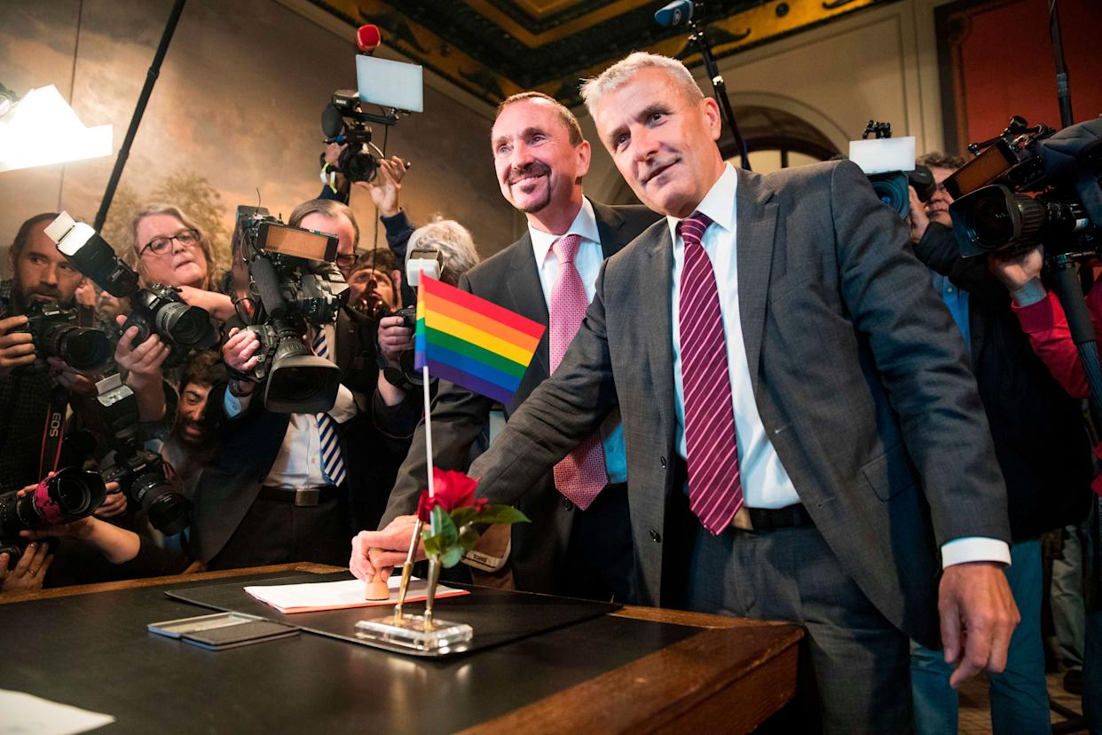 Bode Mende (R) and Karl Kreile stamp their marriage certificate as they became Germany's first gay couple to be legally married tying the knot at the Schoeneberg town hall in Berlin on October 1, 2017.. Germany celebrates its first gay marriages as same-sex unions become legal after decades of struggle. Local authorities rushed to get weddings underway as soon as possible, after lawmakers voted on June 30th to give Germany's roughly 94,000 same-sex couples the right to marry. / AFP PHOTO / Odd ANDERSEN (Photo credit should read ODD ANDERSEN/AFP/Getty Images)