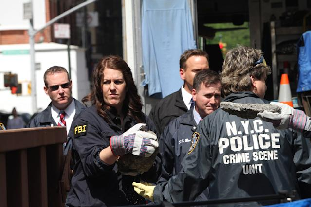 Members of the FBI and NYPD carry pieces of concrete out of a basement of a building on the corner of Wooster Street and Prince Street in Manhattan during a renewed investigation into the 1979 disappearance of 6-year-old Etan Patz, on Friday, April 20, 2012 in New York. Patz vanished after leaving his family's home for a short walk to his school bus stop. NYPD spokesman Paul Browne says the building being searched for his remains is about a block from where the family lived. (AP Photo/Mary Altaffer)