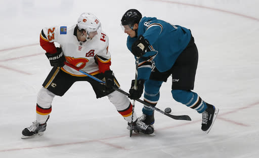 Calgary Flames'Sean Monahan (23) battles for the puck against the San Jose Sharks' Justin Braun (61) in the second period of an NHL hockey game in San Jose, Calif., Sunday, March 31, 2019. (AP Photo/Josie Lepe)