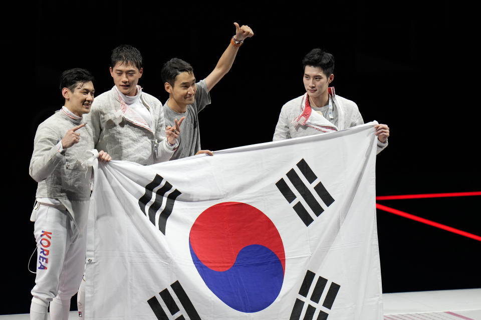South Korea team celebrate defeating Italy and won the gold medal in the men's individual Sabre team bronze medal competition at the 2020 Summer Olympics, Tuesday, July 27, 2021, in Chiba, Japan. (AP Photo/Hassan Ammar)