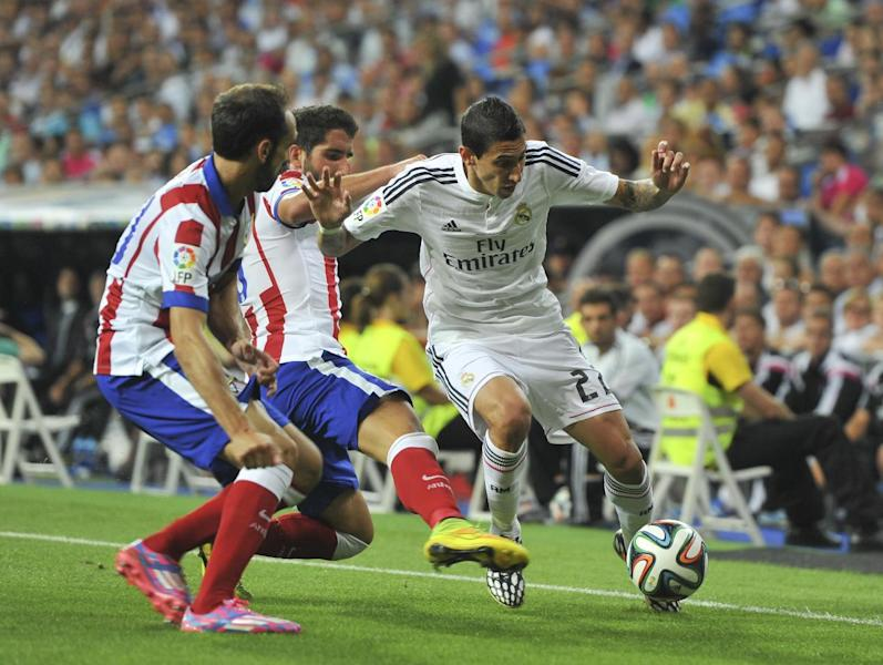 Real Madrid midfielder Angel di Maria (R) is challenged by two Atletico Madrid players during their Spanish SuperCup first leg at the Santiago Bernabeu stadium in Madrid, on August 19, 2014 (AFP Photo/Dani Pozo)