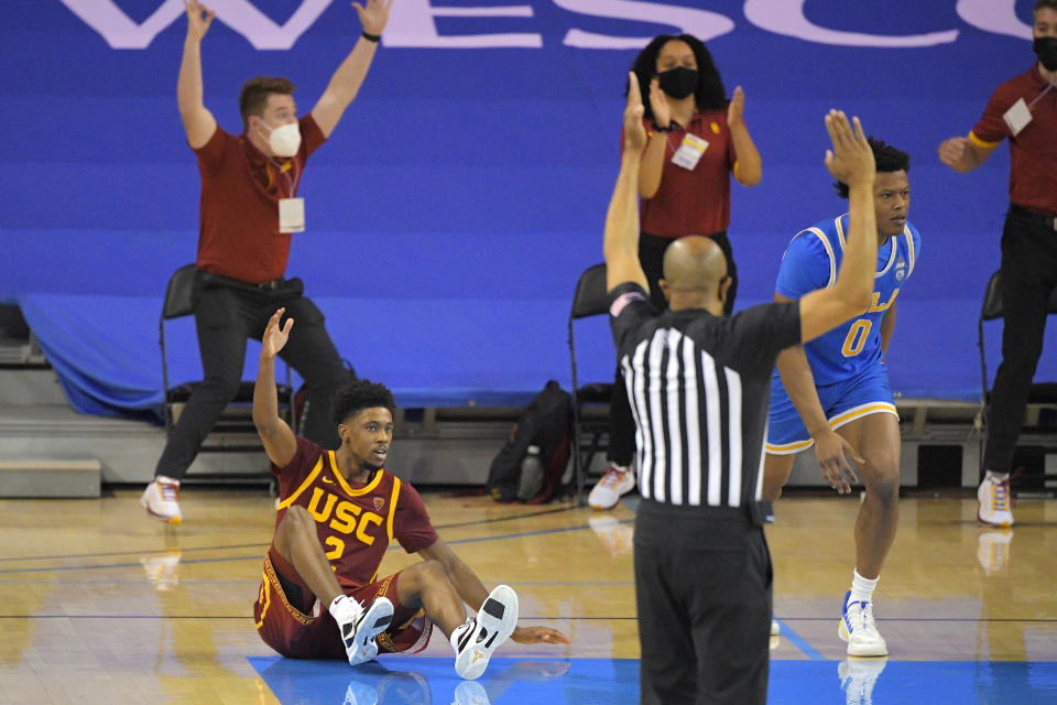Southern California guard Tahj Eaddy, left, reacts after making a game-winning three-point shot as UCLA guard Jaylen Clark runs down court during the second half of an NCAA college basketball game Saturday, March 6, 2021, in Los Angeles. USC won 64-63. (AP Photo/Mark J. Terrill)