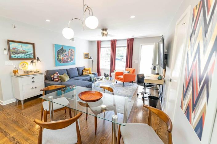 A living room at 510 Queens has art by Nico Amortegui above the couch and a paint-by-number from Sleepy Poet above the side table.