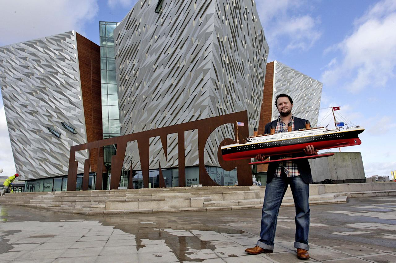 "FILE In this Wednesday, March 7, 2012 file photo Justin Lowry holds his model of the Titanic which will be one of many object on display in the the new 100 million pound Titanic Belfast visitor center, Belfast, Northern Ireland. Celebrating the ship and the people who built her is the aim of Titanic Belfast, a shiny new ""visitor experience"" _ don't call it a museum _ whose four prow-like wings jut jauntily skyward beside the River Lagan on the site of the old Harland and Wolff shipyard. Titanic, the world's largest, most luxurious ocean liner, left this spot on April 2, 1912 on its maiden voyage from England to New York. Twelve days later, it stuck an iceberg off the coast of Newfoundland and sank in the early hours of April 15. More than 1,500 of the 2,200 people on board died. (AP Photo/Peter Morrison)"