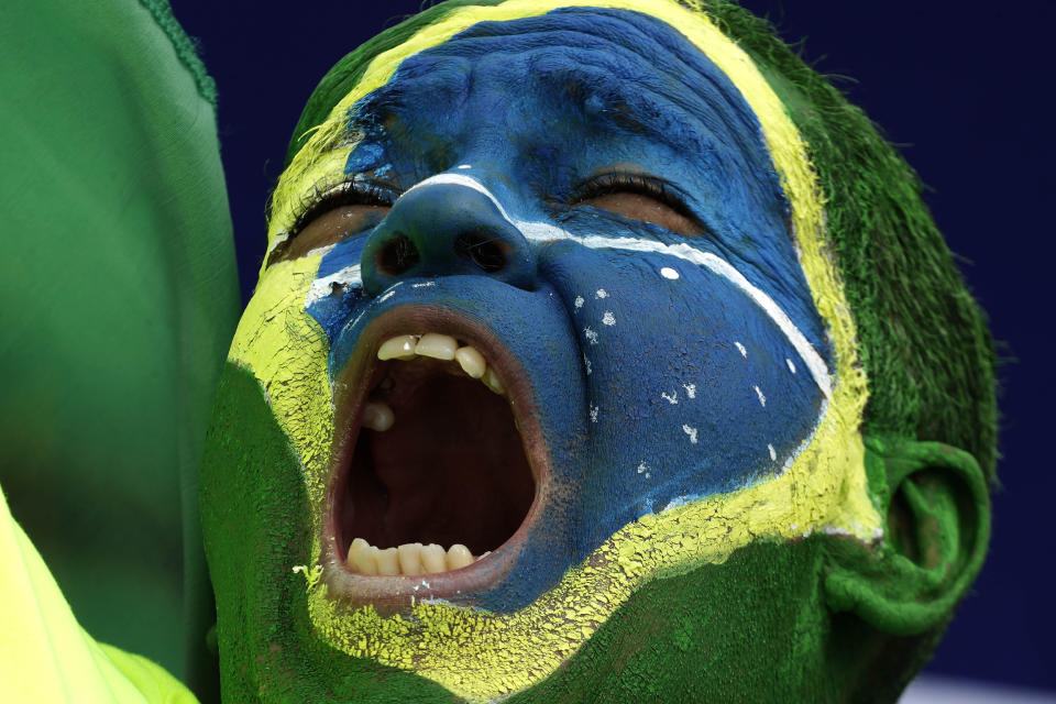 A demonstrator with the Brazilian flag painted on his face, shouts slogans during a caravan backing President Jair Bolsonaro's anti-coronavirus-lockdown stance, marking May Day, or International Workers' Day, in Brasilia, Brazil, Saturday, May 1, 2021. (AP Photo/Eraldo Peres)