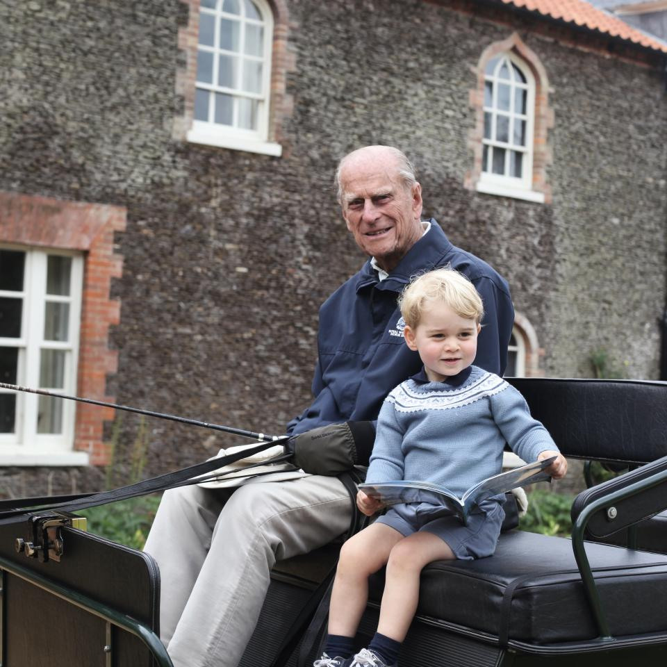 Prince Philip sits with Prince George in a carriage