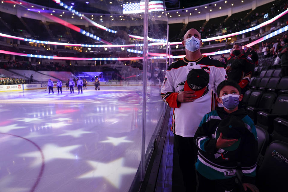 Fans listen to the national anthem before an NHL hockey game between the Anaheim Ducks and the Vegas Golden Knights, Saturday, April 24, 2021, in Anaheim, Calif. (AP Photo/Jae C. Hong)