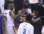 Toronto Raptors center Serge Ibaka (9) consoles Golden State Warriors forward Kevin Durant (35) as Durant leaves with a leg injury in the first half of Game 5 of the NBA Finals in Toronto, Monday, June 10, 2019. (Frank Gunn/The Canadian Press via AP)