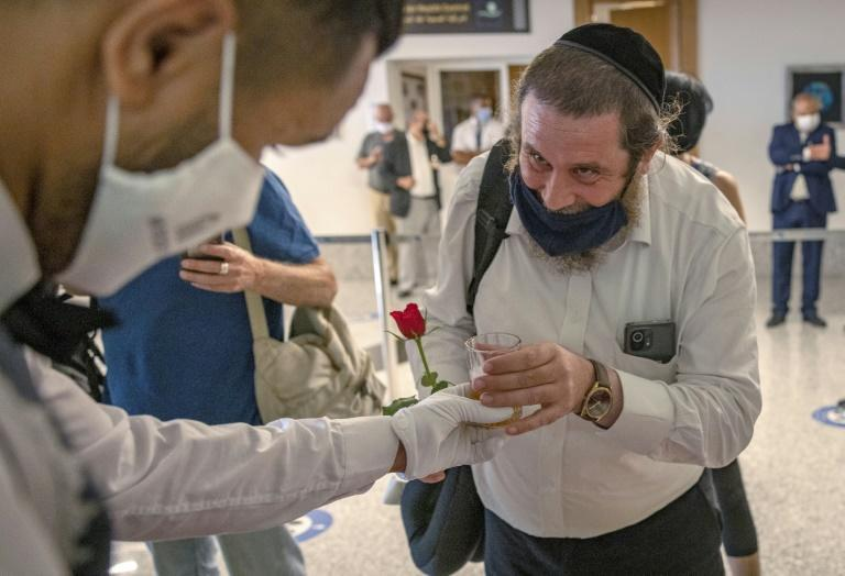 An Israeli tourist is welcomed in Morocco with a rose and a beverage after arriving on the first direct commercial flight between the two countries
