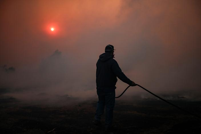 A worker wets the ground in a ranch as the Easy Fire spreads in Simi Valley, North of Los Angeles, Calif., on Oct. 30, 2019. (Photo: Etienne Laurent/EPA-EFE/Shutterstock)