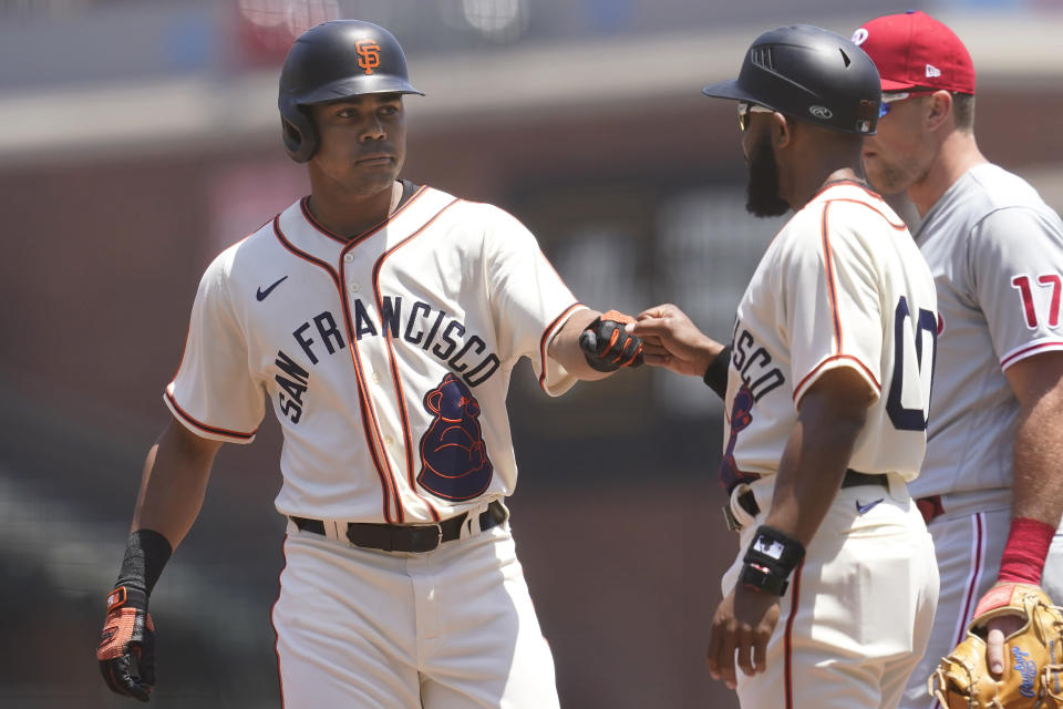 San Francisco Giants' LaMonte Wade Jr., left, is congratulated by first base coach Antoan Richardson after hitting a single against the Philadelphia Phillies during the first inning of a baseball game in San Francisco, Saturday, June 19, 2021. The Giants are wearing San Francisco Sea Lions jerseys to honor Juneteenth on African American Heritage Day. (AP Photo/Jeff Chiu)