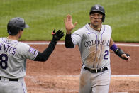 Colorado Rockies' Yonathan Daza (2) celebrate with teammate Joshua Fuentes after scoring on a triple by Charlie Blackmon during the fourth inning of a baseball game against the Pittsburgh Pirates in Pittsburgh, Sunday, May 30, 2021. (AP Photo/Gene J. Puskar)