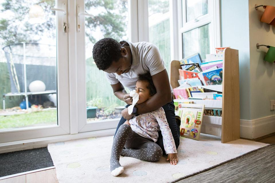 A young mixed race girl getting her Ethiopian dad, to wipe her runny nose whilst playing together at home.
