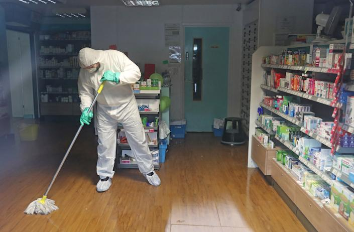 """A man in protective clothing cleaning the County Oak Medical Centre GP practice in Brighton which has been temporarily closed """"because of an urgent operational health and safety reason"""", following reports a member of staff there was one of those infected with coronavirus."""