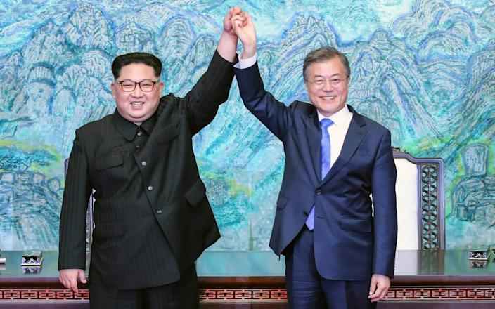 North Korean leader Kim Jong Un, left, and South Korean President Moon Jae-in raising their hands after signing a joint statement at the border village of Panmunjom, April 27 2018 - Korea Summit Press Pool