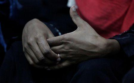 Eritrean migrant Minya Mesmer touches a ring on her hand at a military building in Misrata