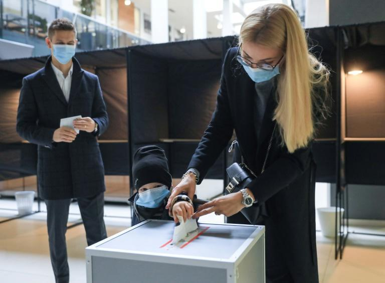 A woman and a child cast a ballot during the second round of the parliamentary elections in Lithuanian capital Vilnius