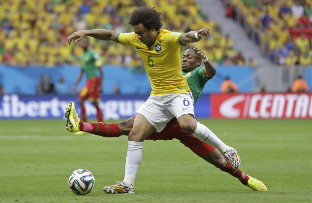 Brazil's Marcelo, left, is challenged by Cameroon's Eyong Enoh during the group A World Cup soccer match between Cameroon and Brazil at the Estadio Nacional in Brasilia, Brazil, Monday, June 23, 2014. (AP Photo/Andre Penner)
