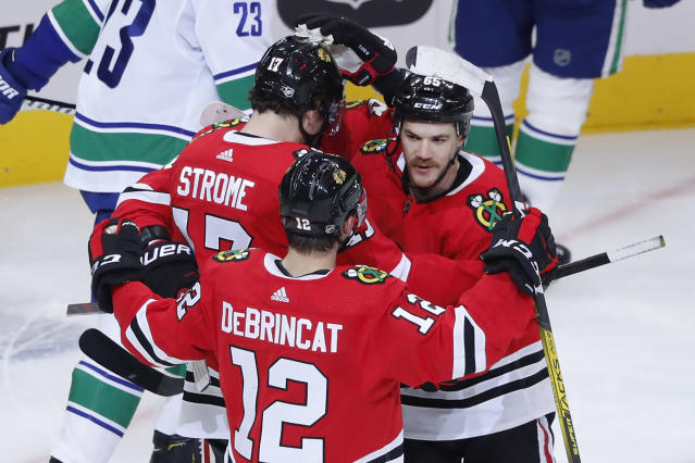 Chicago Blackhawks' Alex DeBrincat (12) celebrates with Andrew Shaw after Shaw's goal during the first period of an NHL hockey game against the Vancouver Canucks, Thursday, Nov. 7, 2019, in Chicago. (AP Photo/Charles Rex Arbogast)