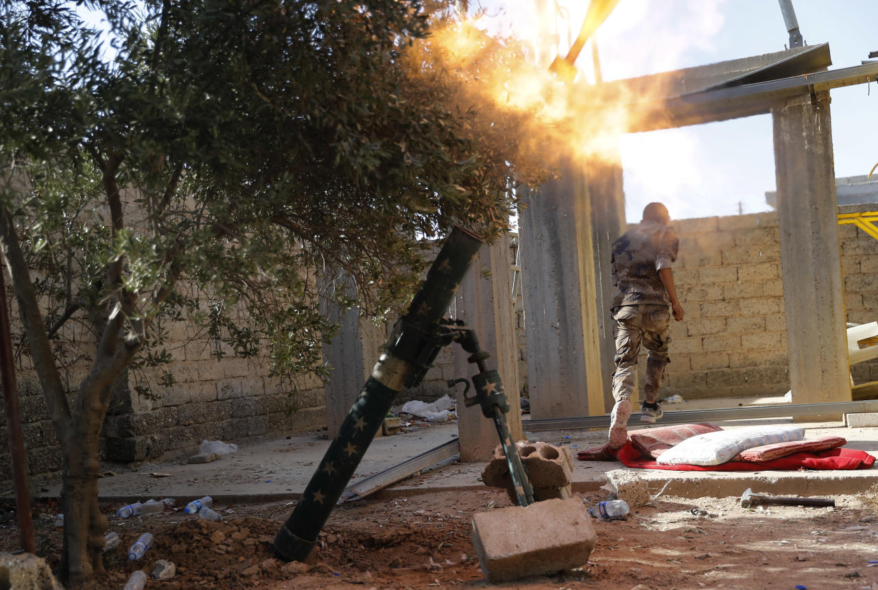 "FILE - In this July 27, 2017 file photo, a U.S.-backed Syrian Democratic Forces fighter, runs as he fires mortars at Islamic State group militant, in Raqqa, northeast Syria. The Syrian Democratic Forces said in a statement Wednesday, Sept. 20, 2017, that the battle for the Islamic State group's de-facto capital, Raqqa, has reached its ""final stages"" with the opening of a new front. (AP Photo/Hussein Malla, File)"