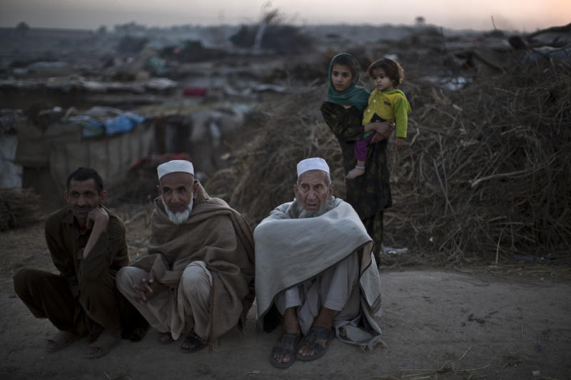 Pakistani men, who were displaced with their families from Pakistan's tribal areas due to fighting between the Taliban and the army, sit on a roadside on the outskirts of Islamabad, Pakistan, Saturday, Nov. 2, 2013. The Pakistani Taliban confirmed the death of their leader, Hakimullah Mehsud, in a U.S. drone strike Saturday, a day after he was killed, as the group's leadership council met to begin the process of choosing a successor. (AP Photo/Muhammed Muheisen)
