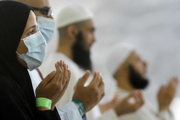 """FILE - In this Thursday, Oct. 17, 2013, file photo, Egyptian Muslim pilgrims, some wearing masks as a precaution against the Middle East respiratory syndrome, pray after they cast stones at a pillar, symbolizing the stoning of Satan, in a ritual called """"Jamarat,"""" the last rite of the annual hajj, in Mina near the Muslim holy city of Mecca, Saudi Arabia. Saudi Arabia's King Abdullah sacked the country's health minister on Monday, April 21, 2014, amid a spike in deaths and infections from the virus known as the Middle East respiratory syndrome, or MERS. The official Saudi Press Agency carried the royal order that said Abdullah al-Rabiah was relieved of his post as Health Minister, and that Labor Minister Adel Faqih will temporarily take over the health minister's portfolio until a replacement is named. The statement said al-Rabiah is now adviser to the Royal Court. (AP Photo/Amr Nabil, File)"""