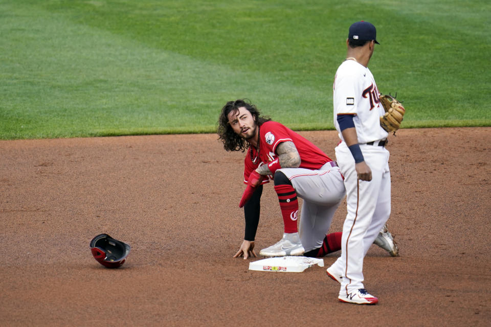 Cincinnati Reds' Jonathan India, left, loses his helmet as he steals second base against Minnesota Twins' Jorge Polanco in the first inning of a baseball game, Monday, June 21, 2021, in Minneapolis. (AP Photo/Jim Mone)