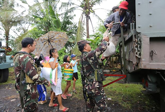 <p>Soldiers assist residents to board a military truck as they prepare to depart to the evacuation center after Mayon volcano erupted anew, in Padang town, Albay province, Philippines, Jan.16, 2018. (Photo: Stringer/Reuters) </p>