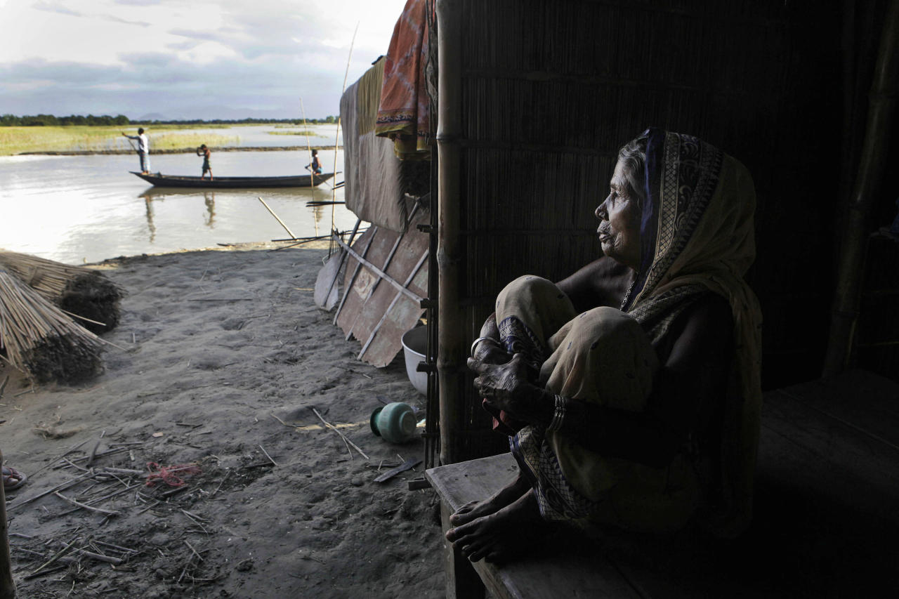 Indian woman Anowara Bewa, 65, sits inside a makeshift temporary hut in the flood affected Gagalmari village in Assam state, India, Monday, July 2, 2012. The floods from monsoon rains in northeastern India killed dozens of people, with more than 2,000 villages inundated as rivers breached their banks, an official said Sunday. (AP Photo/Anupam Nath)