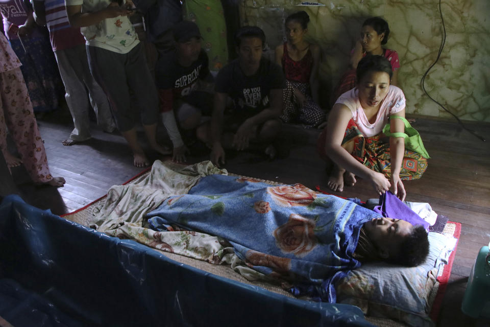 Friends and relatives mourn Saturday, March 27, 2021, over the body of Kyaw Htet Aung, 17 years old, who was fatal shot Friday, in the neck by soldiers in Dala Township, Yangon, Myanmar Myanmar security forces reportedly killed 93 people Saturday in the deadliest day since last month's military coup. (AP Photo)