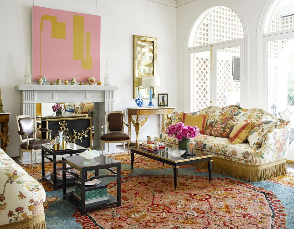 "<p>Warm, silky white walls create an airy canvas for a vibrant painting by Pete Jordan and a decorative Oushak rug in this <a href=""https://www.veranda.com/home-decorators/a29416531/kimberly-schlegel-whitman-dallas-home-tour/"">Dallas family room</a> designed by <a href=""https://www.janshowers.com/"">Jan Showers</a>. To make the expansive room feel less daunting, architect <a href=""https://www.wilsonfuqua.com/"">J. Wilson Fuqua</a> added custom crown moldings—depicting tassels and latticework—to bring a playful element to the space. The sofa is upholstered in a flamboyant <a href=""https://www.fschumacher.com/"">Schumacher</a> floral linen with <a href=""https://samuelandsons.com/"">Samuel & Sons</a> fringe.</p>"