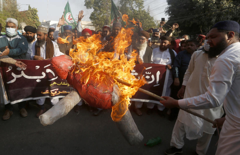 Supporters of Sunni Tehreek, a religious group, burn an effigy of French President Emmanuel Macron during a protest against the Macron and the republishing of caricatures of the Prophet Muhammad they deem blasphemous, in Lahore, Pakistan, Sunday, Nov. 1, 2020. (AP Photo/K.M. Chaudary)
