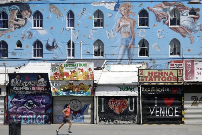 A man jogs in front of closed-off store fronts on March 29, 2020, in the Venice Beach section of Los Angeles. (Marcio Jose Sanchez/AP)