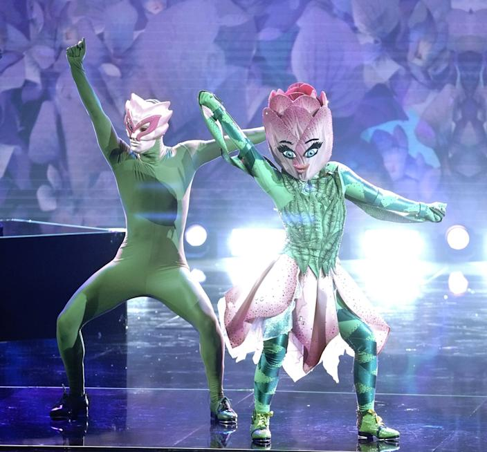 Two people in green leotards with tulip headdresses dance on stage.