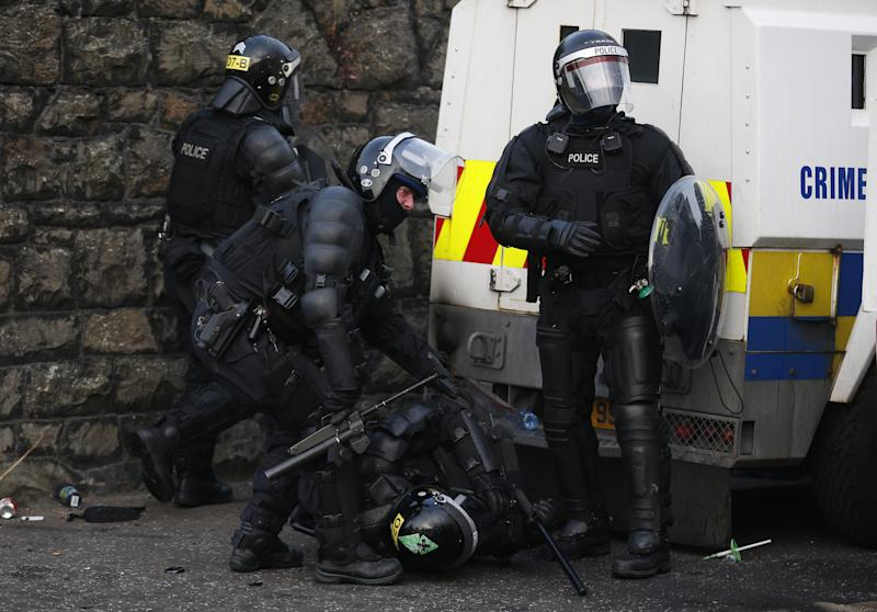 An injured police officer after being attacked by loyalist's close to the Ardoyne area of North Belfast, Northern Ireland, Friday, July 12, 2013. Protestant hardliners attacked lines of Belfast riot police Friday as Northern Ireland's annual mass marches by the Orange Order brotherhood reached a furious, chaotic end with running street battles at several urban conflict zones. (AP Photo/Peter Morrison)