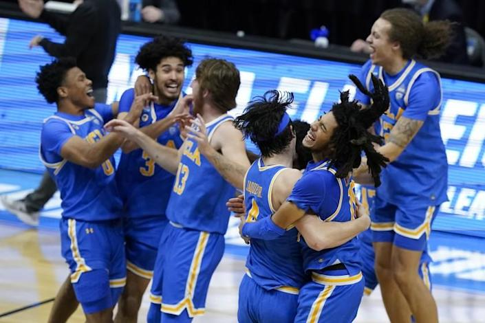 UCLA guard Tyger Campbell, right, celebrates with teammate guard Jaime Jaquez Jr. (4) after an Elite 8 game against Michigan in the NCAA men's college basketball tournament at Lucas Oil Stadium, Wednesday, March 31, 2021, in Indianapolis. UCLA won 51-49. (AP Photo/Darron Cummings)