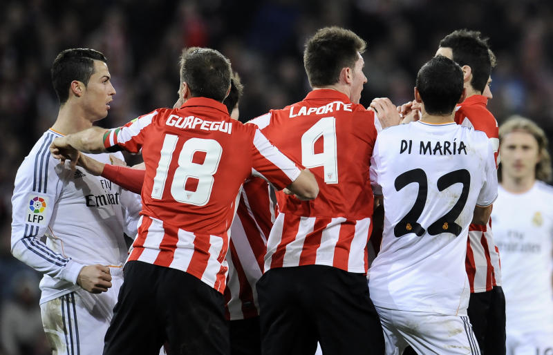 Real Madrid's Cristiano Ronaldo of Portugal, left, reacts with Athletic Bilbao's Carlos Gurpegi, second left, during their Spanish League soccer match against Athletic Bilbao, at San Mames stadium in Bilbao, Spain, Sunday, Feb. 2, 2014. (AP Photo/Alvaro Barrientos)