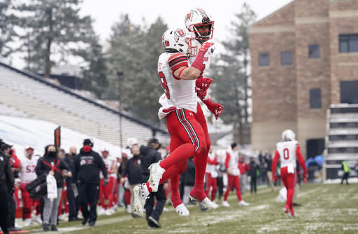 Utah wide receiver Britain Covey, front, celebrates catching a pass for a touchdown with wide receiver Bryan Thompson in the second half of an NCAA college football game against Colorado Saturday, Dec. 12, 2020, in Boulder, Colo. Utah won 38-21. (AP Photo/David Zalubowski)
