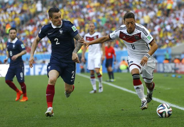 Germany's Mesut Ozil (R) fights for the ball with France's Mathieu Debuchy during the 2014 World Cup quarter-finals at the Maracana stadium in Rio de Janeiro July 4, 2014. REUTERS/Darren Staples (BRAZIL - Tags: SOCCER SPORT WORLD CUP)