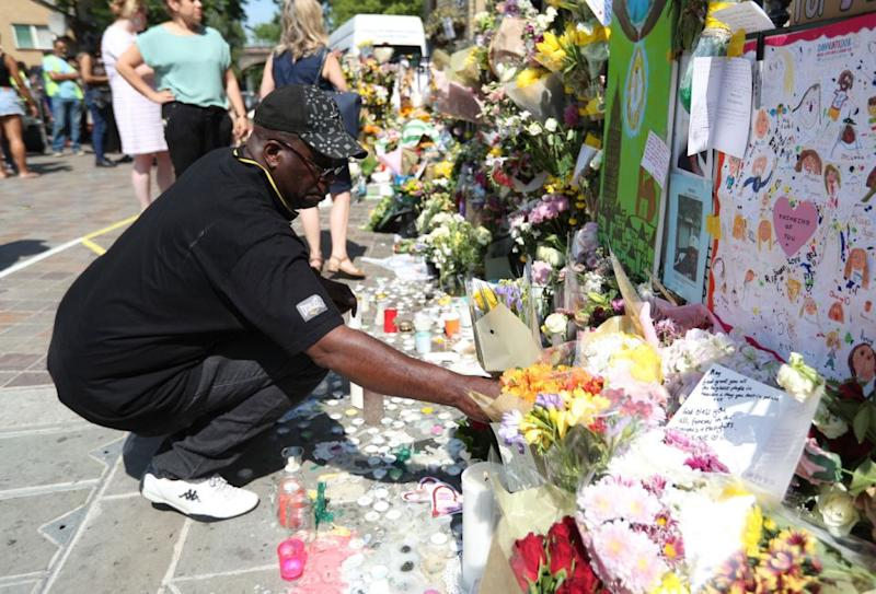 A man lays flowers in tribute of those who have died at Grenfell Tower in north Kensington. Picture: AAP