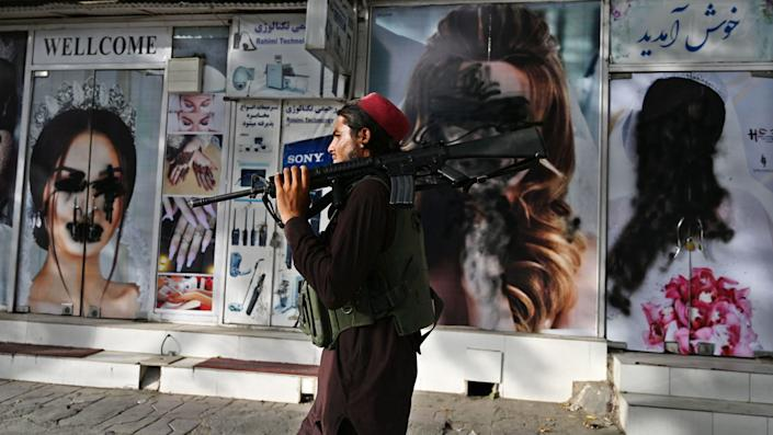 A Taliban fighter walks past a beauty salon with pictures of women destroyed by a spray-paint in Shar-e-Naw in Kabul on August 18, 2021. (Wakil Kohsar / AFP via Getty Images)