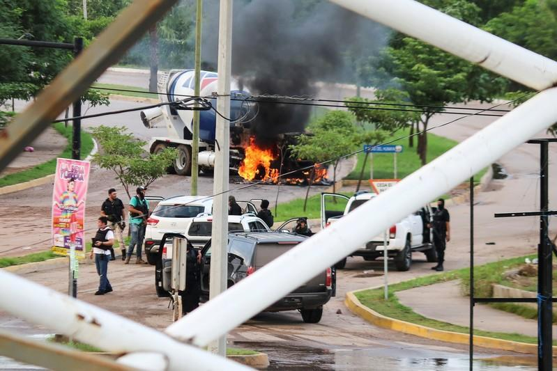 """Cartel gunmen are seen near a burning truck during clashes with federal forces following the detention of Ovidio Guzman, son of drug kingpin Joaquin """"El Chapo"""" Guzman, in Culiacan"""