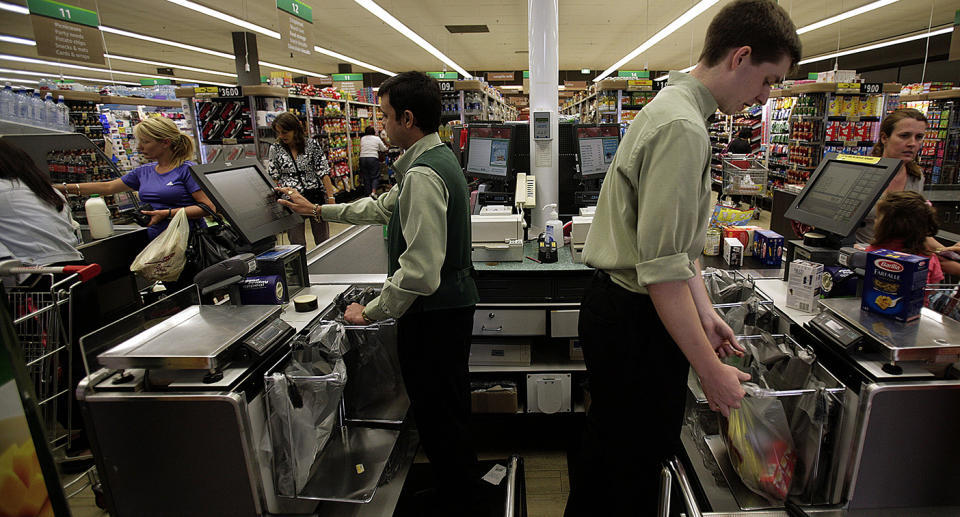 Employees ring through customers' purchases at the checkout counter at a Woolworths in Melbourne.
