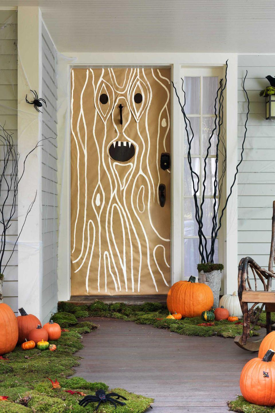 """<p>Trick out your front porch with a layer of moss, spiderwebs and critters — plus a menacing tree trunk on the door. Use painter's tape to affix <span class=""""redactor-unlink"""">brown kraft paper</span> onto your door, making slits for the handle and knocker. Cut eyes and a mouth out of black construction paper; tape or glue them onto the kraft paper. For the wood grain: Take white craft paint and draw curved lines first around the facial features, then vertically on the door. Place <span class=""""redactor-unlink"""">preserved green moss</span> along the edges of your front steps or porch.</p>"""